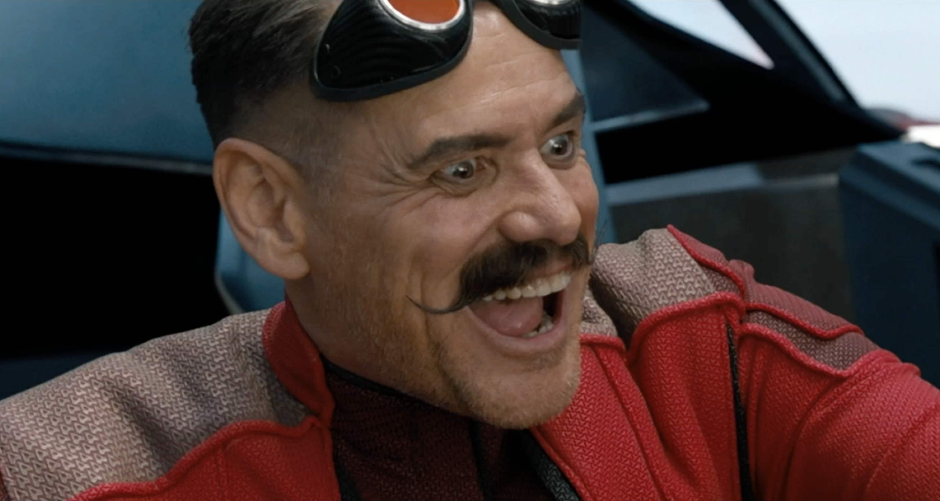 Jim Carrey as Dr. Robotnik, giddy in an aircraft with a mischievous, shit-eating grin